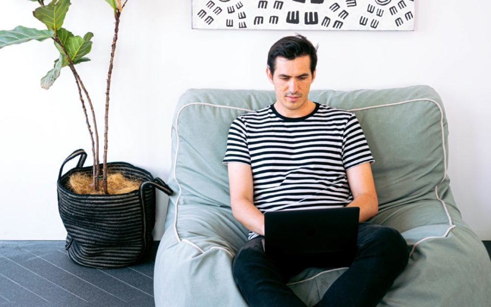 Man in striped shirt sitting on blue beanbag chair working on laptop
